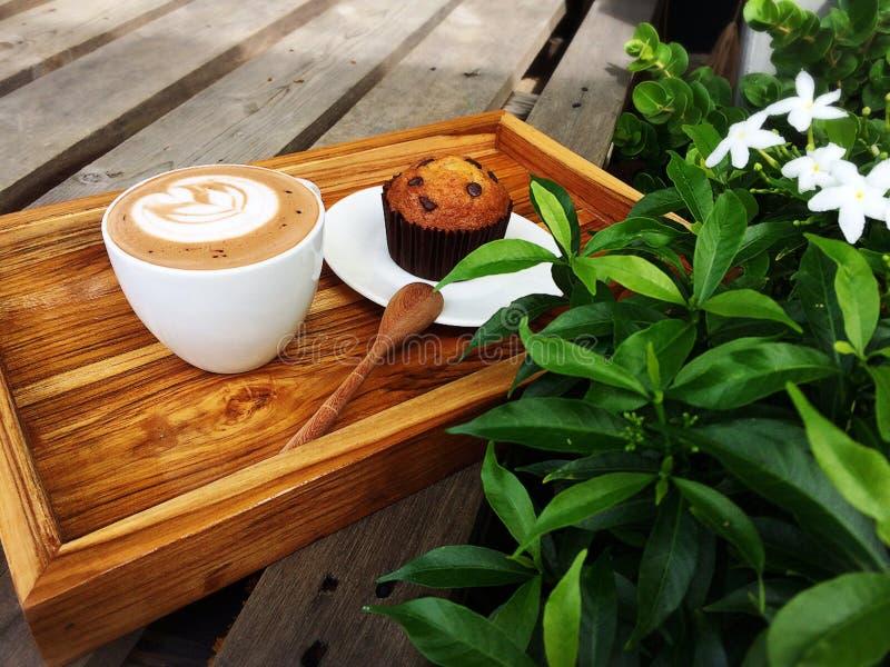 De koffie van de Lattekunst, houten lepel en de kopcake van de Banaanchocolade royalty-vrije stock foto