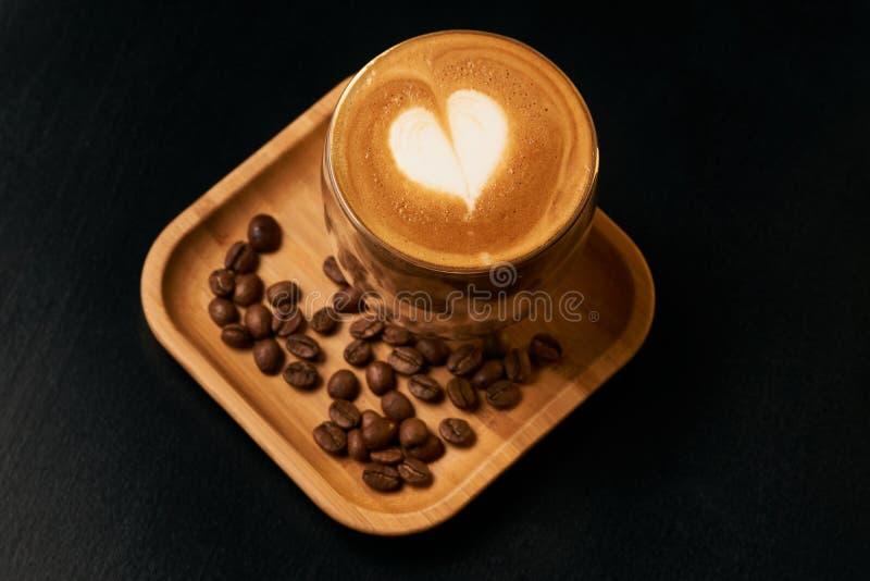 De koffie van de Lattekunst met hart-vormig melkschuim dat wordt verfraaid stock afbeeldingen