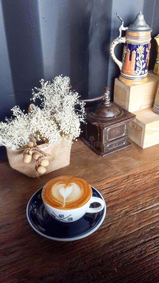 De koffie van de Lattekunst met wit droog die bloem en hartsymbool door barista wordt gemaakt stock foto