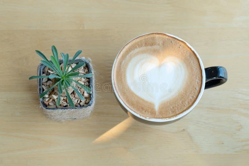 De koffie van de Lattekunst in de ochtendtijd met zonlicht op houten lijstachtergrond bij koffiewinkel royalty-vrije stock fotografie
