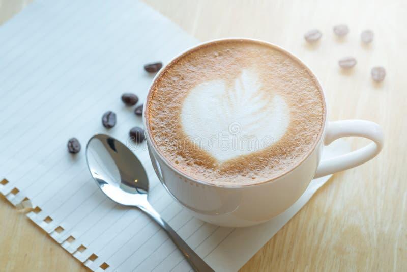 De koffie van de LLattekunst en geroosterde koffiebonen in ochtendtijd met stock afbeelding