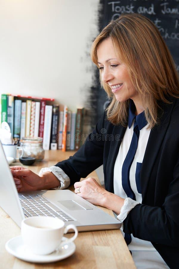 De Koffie van onderneemsterusing laptop in royalty-vrije stock afbeelding
