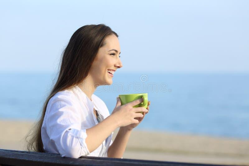 De koffie van de vrouwenholding en het kijken weg op het strand stock afbeeldingen