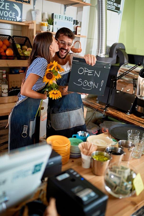 De koffiebar is open - man en vrouweneigenaar met open teken stock fotografie