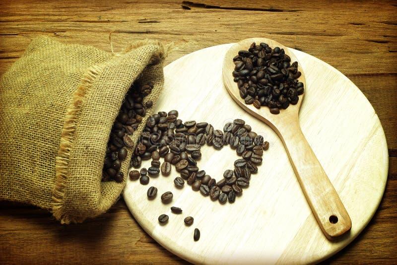 De koffiebonen die van een jute morsen doen en een lepel op een textuur in zakken stock fotografie