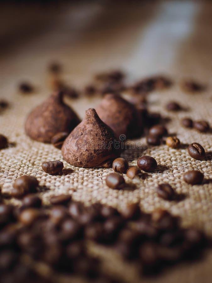 De koffiebonen en het chocoladesuikergoed op jute sluiten omhoog Koffie en snoepjesachtergrond royalty-vrije stock foto