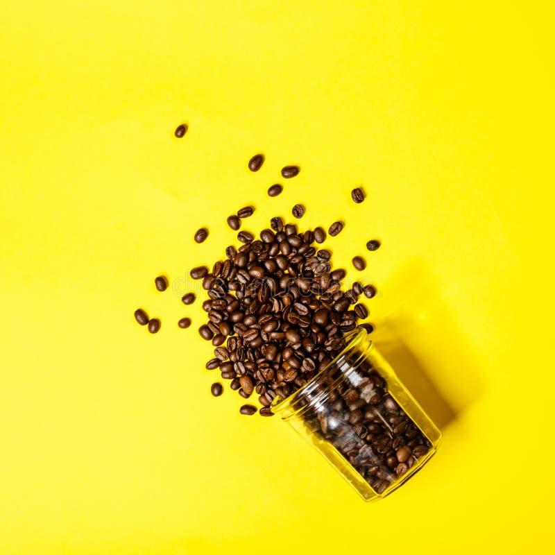 De koffiebonen op gele vlakke achtergrond, leggen, hoogste mening stock afbeeldingen
