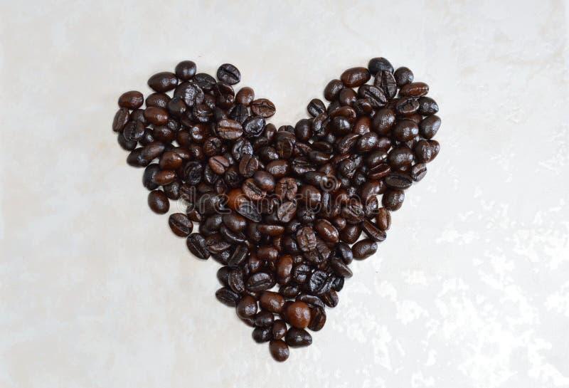 De koffieboon schikt in hartvorm stock afbeelding