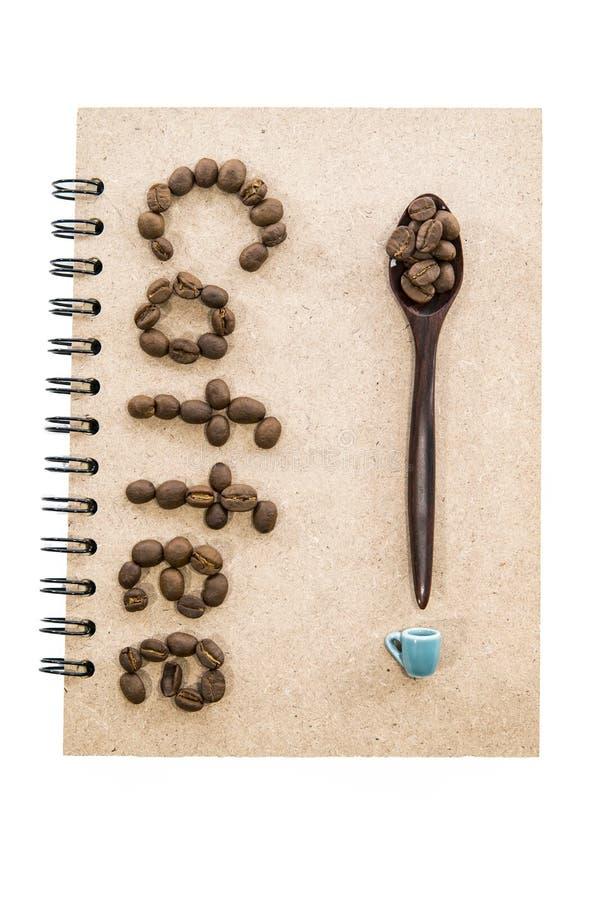 De koffieboon schikt in koffiewoord met lepel en kleine kop stock foto