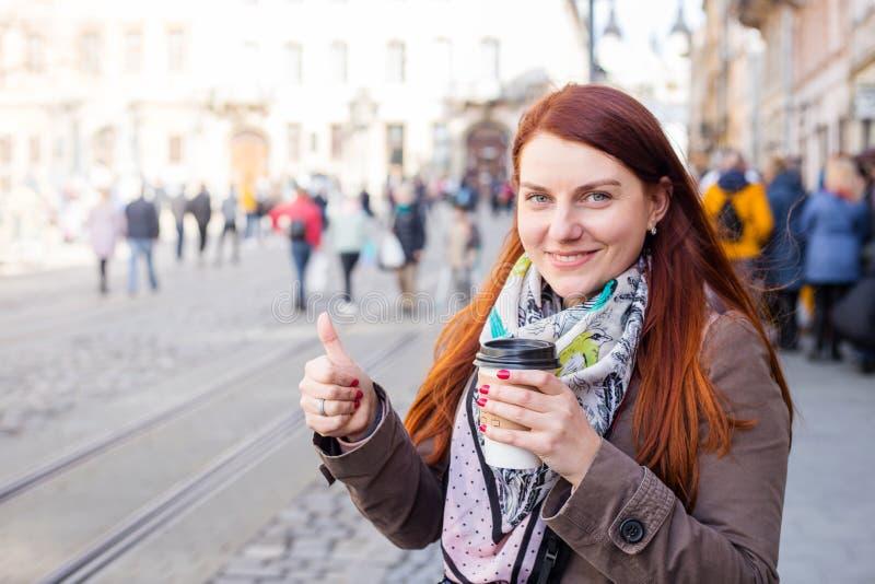 De koffiekop en glimlach van de vrouwenholding op de vage straat Zonnige de lentemiddag Rode manicure stock afbeelding