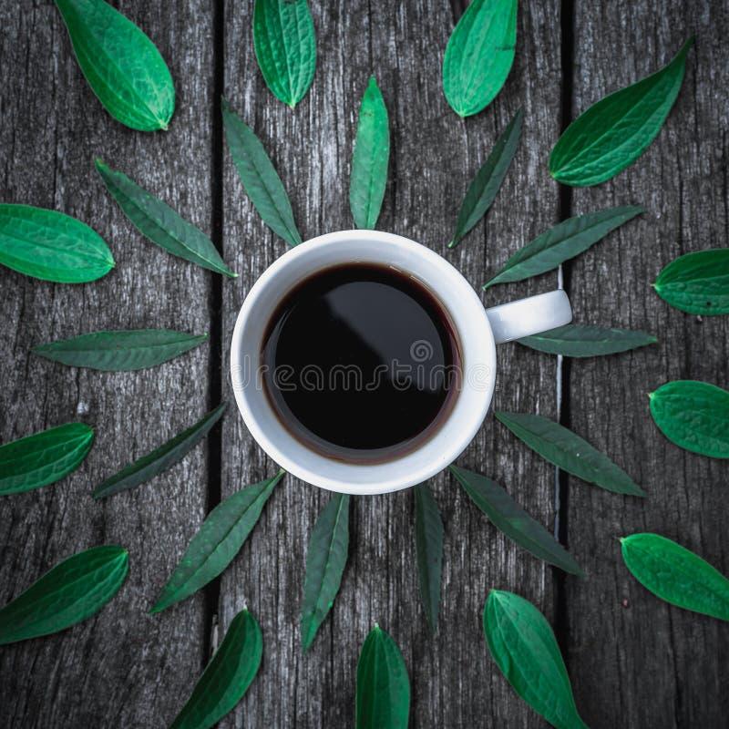 De koffiekop op groene bladerenvlakte als achtergrond lag stock afbeeldingen