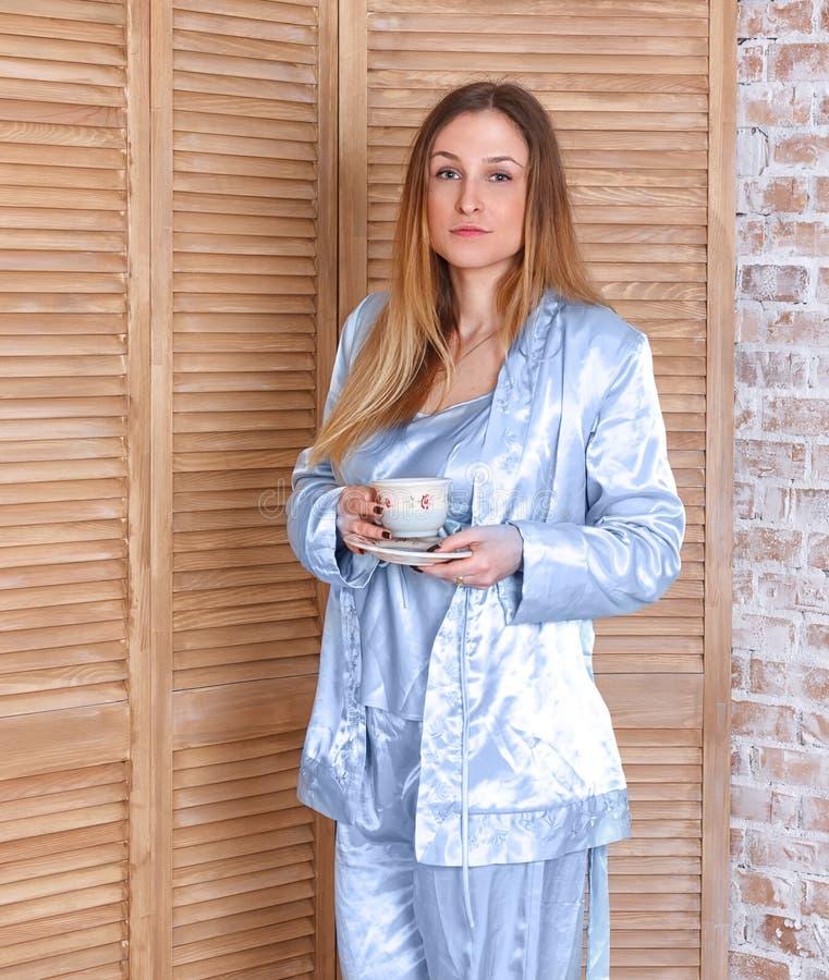 De koffiekop van de vrouwenholding in de ochtend stock foto's