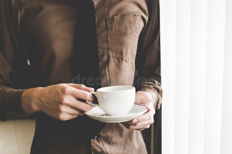 De koffiekop van de zakenmanholding bij venster Creatief Opstarten van bedrijvenidee stock afbeeldingen