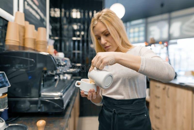 De koffiekunst, close-up van de jonge mooie vrouwelijke melk van de baristaholding voor bereidt kop van koffie voor royalty-vrije stock afbeeldingen