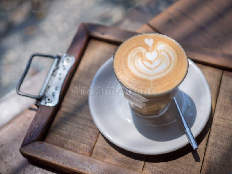 De koffiekunst met hart-vorm patroon in kop op houten lijst in de tuin, sluit omhoog kop van koffiekoffie met hart-vorm patroon royalty-vrije stock foto's