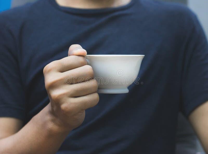 De koffiemok van de mensenholding ter beschikking op donkere overhemdsachtergrond Uitstekende mokken voor uw ontwerp stock afbeelding
