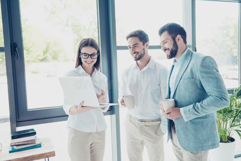 De koffiepauze in bureau, drie vrolijke collega's heeft heet stock foto