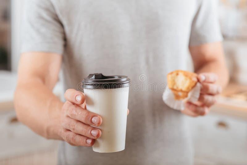 De koffiepauze haalt de beschikbare kop van de mensenmuffin weg royalty-vrije stock foto