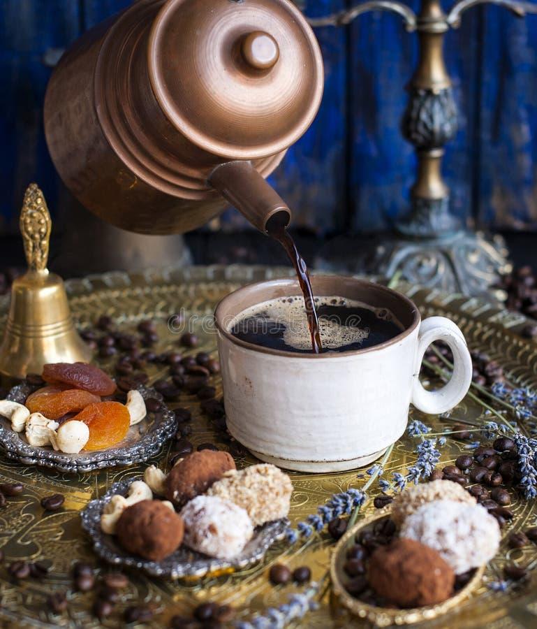 De koffiepot giet de koffie in de kop in de oosterse stijl met de hand gemaakt suikergoed, droge vruchten en bloemen foto in stock afbeeldingen