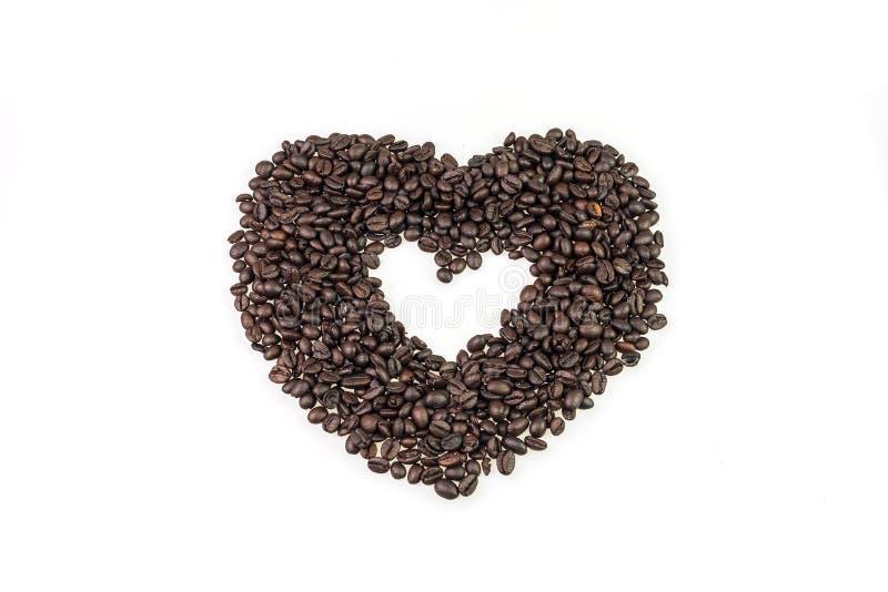 De koffiezaden schikken is hart en witte kop van koffie stock afbeeldingen