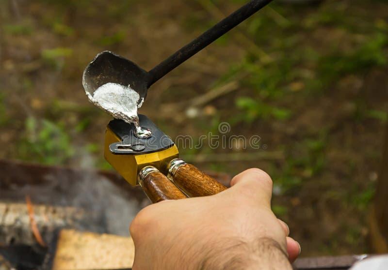 De kogel die om projectiel voor historische wapensmusketten maken het vloeibare metaal wordt gegoten is gevormde in hand vorm teg stock afbeeldingen
