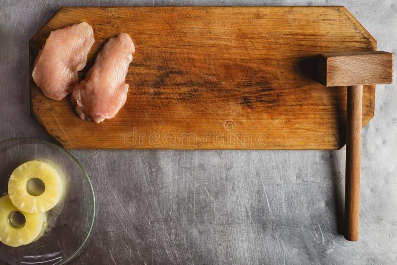 De kok bereidt kip op een houten scherpe raad voor, kip, ananas, vleesvermalser recept voor kippenfilet met kaas en stock foto's