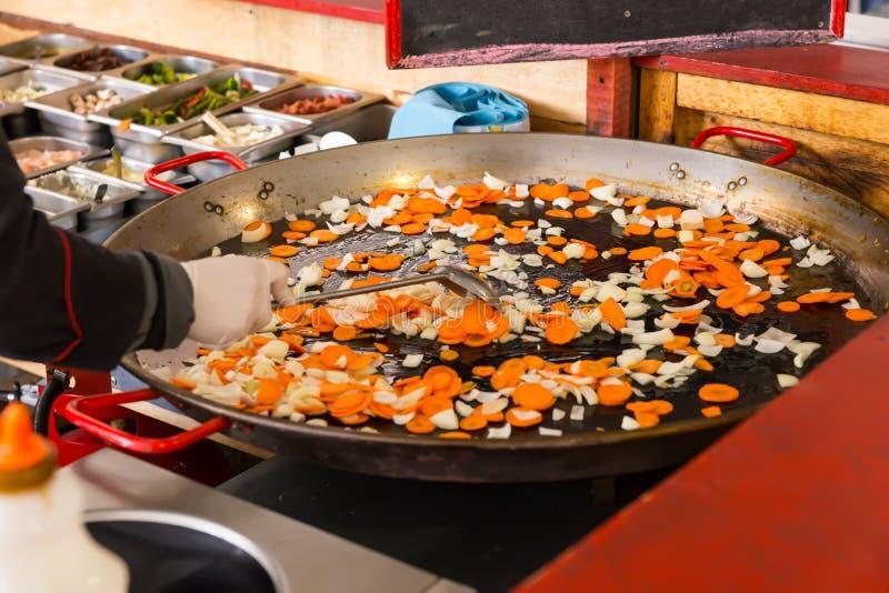 De kok beweegt bradende verse groenten stock afbeelding