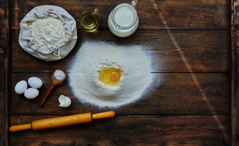 De kok brak een ei in de bloem om een deeg te maken royalty-vrije stock afbeeldingen