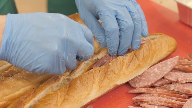 De kok die van de handenchef-kok stukkenworst in baguette in de close-up van de restaurantkeuken zetten royalty-vrije stock fotografie
