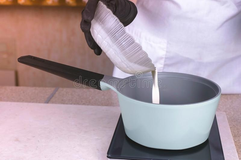 De kok giet de room van de kom in de opnieuw te verwarmen steelpan Dient zwart rubberhandschoenenclose-up in royalty-vrije stock afbeelding