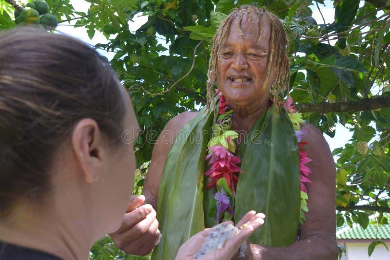 De kok Islander verklaart aan een toeristenvrouw over de Noni-vruchten royalty-vrije stock afbeelding
