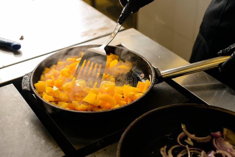 De kok mengt de producten in een pan, het het koken procédé in een restaurant stock afbeelding