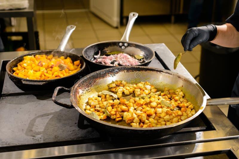 De kok mengt de producten in een pan, het het koken procédé in een restaurant stock afbeeldingen