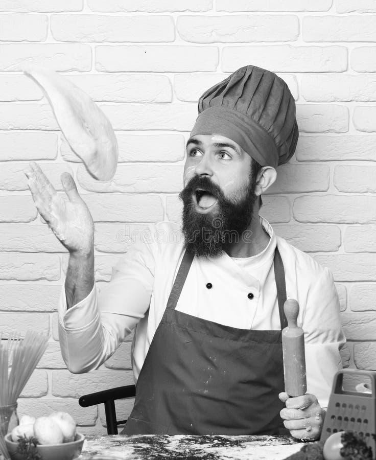 De kok met opgewekt gezicht in eenvormig zit door lijst met groenten houdend deegrol De mens met baard werpt pizzadeeg royalty-vrije stock foto's