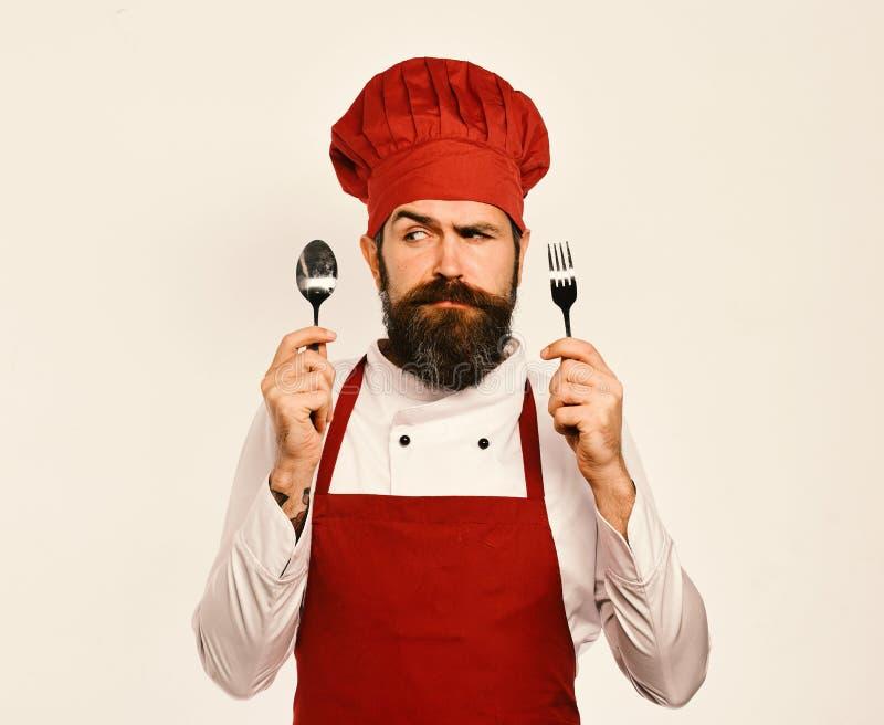 De kok met verward gezicht in eenvormig Bourgondië toont bestek stock afbeeldingen