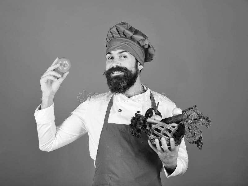 De kok met vrolijk gezicht in eenvormig Bourgondië houdt tomaat stock foto