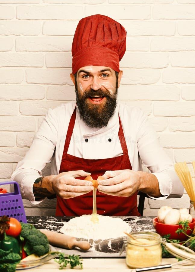 De kok met vrolijk gezicht in eenvormig Bourgondië zit door lijst stock afbeelding