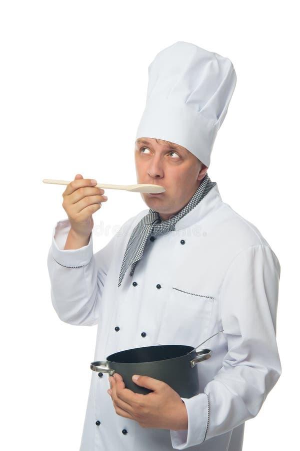 De kok, op witte achtergrond, houdt een pan in zijn hand en probeert een schotel stock foto's