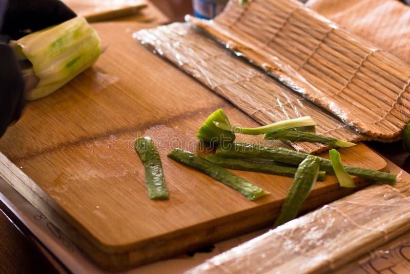 De kok snijdt een komkommer met een mes op een houten raad royalty-vrije stock foto