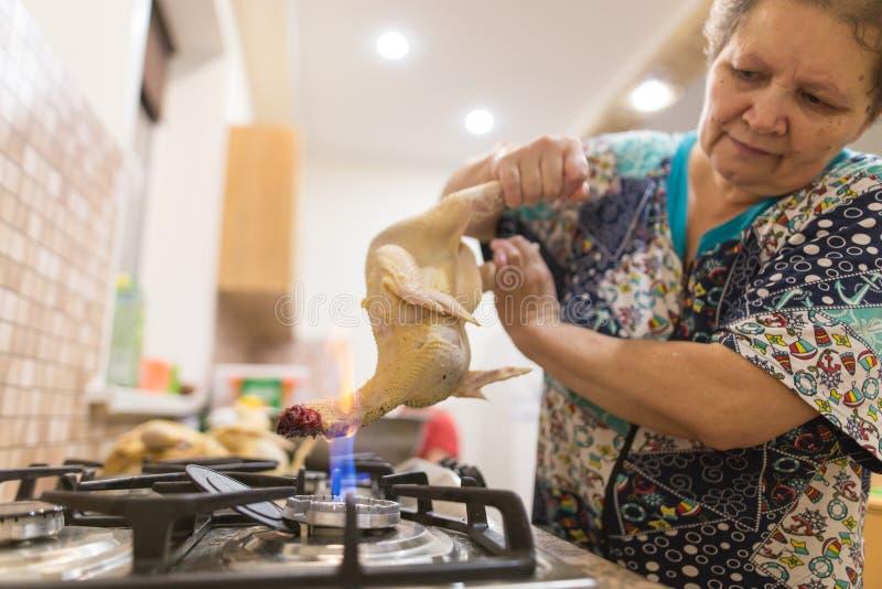 De kok snijdt de kip op brand stock foto