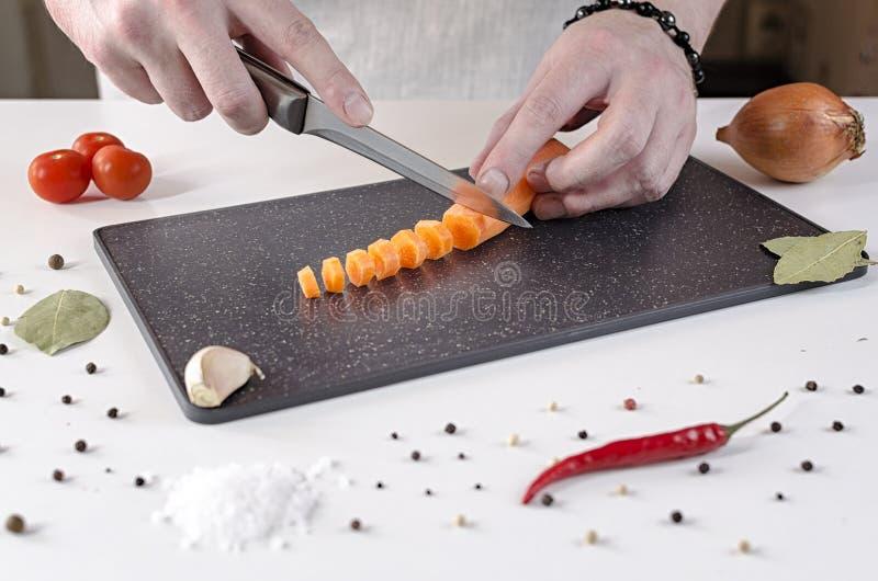 De kok snijdt wortelen in kleine plakken op een zwarte scherpe raad royalty-vrije stock foto's