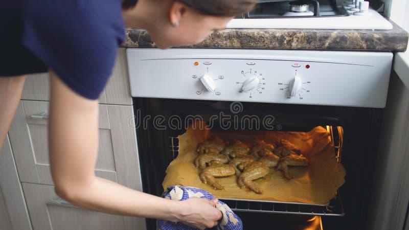 De kok van de huisvrouwenvrouw en controleoven met geroosterde kippenvleugels in de keuken thuis stock afbeeldingen