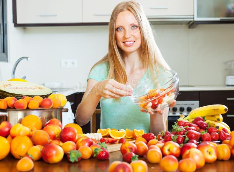 De kokende fruitsalade van het blondemeisje met vruchten royalty-vrije stock afbeeldingen