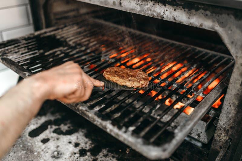 De kokhanden bereidt rokerig vlees op grilloven voor stock fotografie