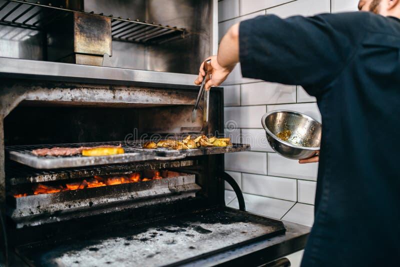 De kokhanden bereidt rokerig vlees op grilloven voor royalty-vrije stock fotografie