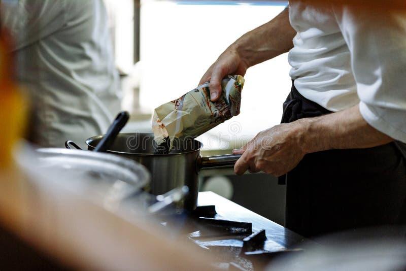 De kokkoks in een restaurantkeuken, bestrooit kruiden in de pan royalty-vrije stock afbeelding