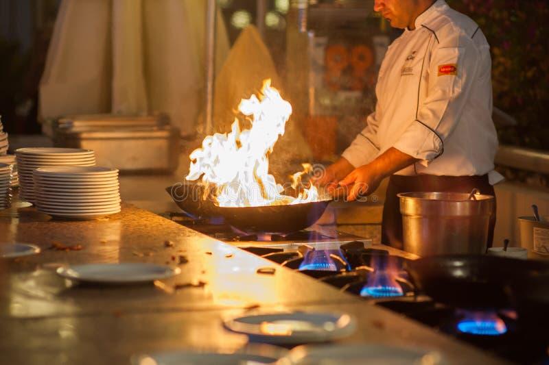 De kokkoks in twee het bakken bladen, gebraden gerechten op hoge hitte stock afbeelding