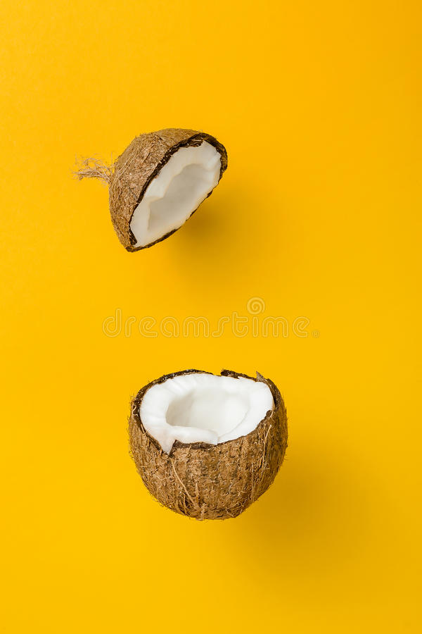 De kokosnoot op gele gekleurde achtergrond, minimale vlakte legt stijl stock afbeeldingen