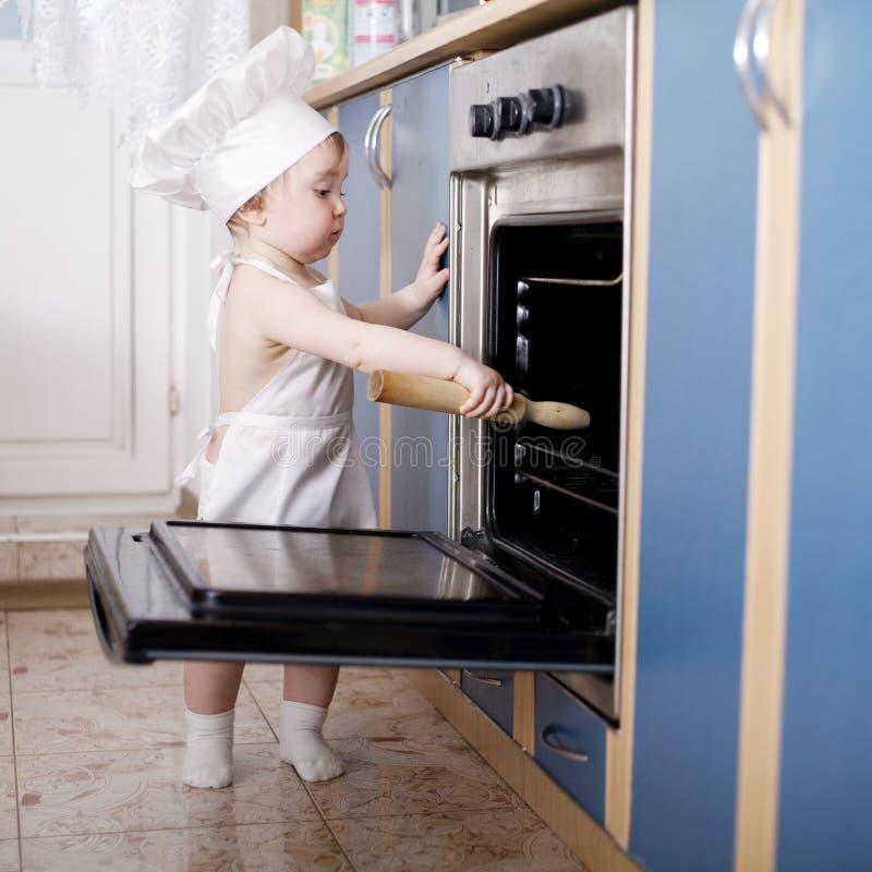 De koks van de babychef-kok in het ovenvoedsel stock afbeelding