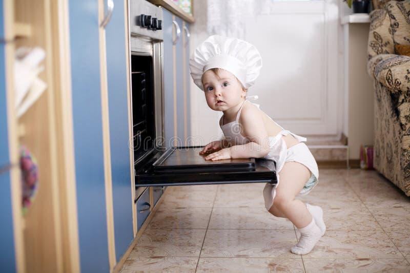 De koks van de babychef-kok in het ovenvoedsel royalty-vrije stock afbeeldingen